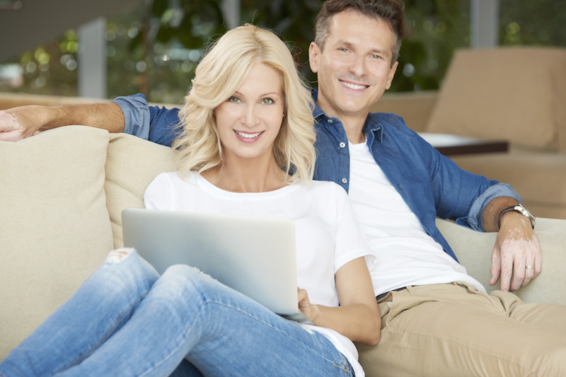 Middle aged couple with attractive smiles sitting on couch after getting porcelain veneers