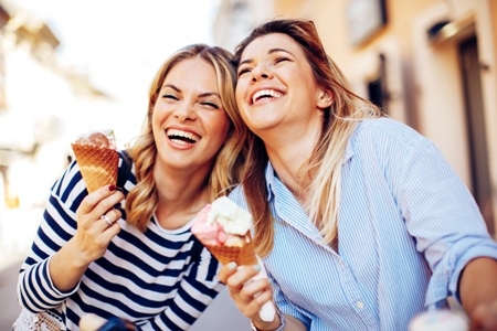 laughing women eating ice cream outdoors
