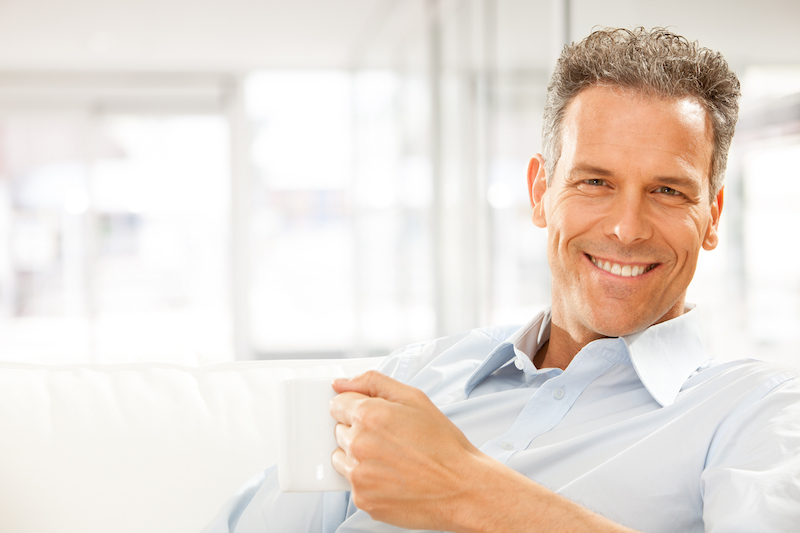 Middle aged man sitting on a couch with a cup of coffee smiling, showing off his white teeth after getting porcelain veneers