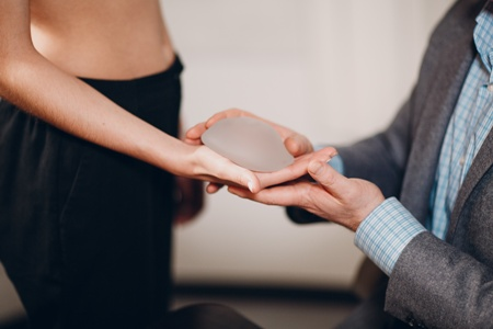 doctor handing silicone breast implant to topless woman