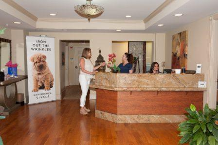 client and staff at front desk of Allure Medi-Spa