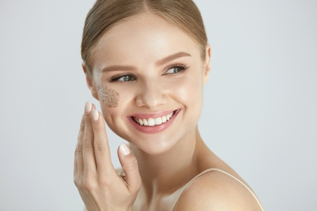 smiling young woman applying skin cream to her face