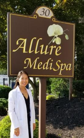 Karyn Kim standing next to the outdoor sign for Allure Medi-Spa