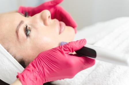 female treatment receiving facial microdermabrasion treatment