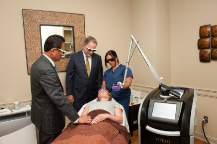 plastic surgeons observing aesthetician performing laser facial rejuvenation