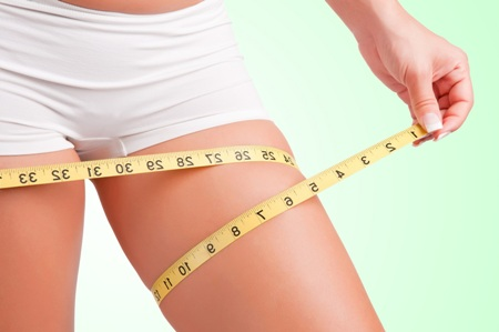 woman wrapping tape measure around her thigh