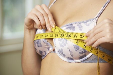 woman in bra measuring her breasts
