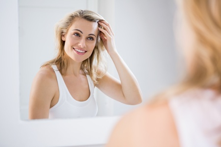 smiling woman looking in the mirror