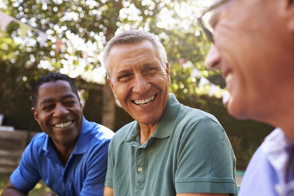 Middle-aged male neighbors smiling and laughing outdoors on a summer evening