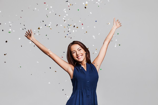 Woman smiling under confetti to celebrate rejuvenated smile