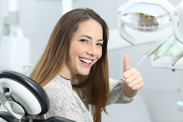 Young dental patient sitting in the treatment chair and smiling while giving the thumbs-up