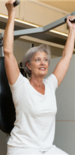 older woman using exercise bar