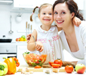woman and young girl in kitchen with healthy food