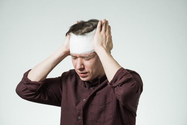 man holding his head after suffering a brain injury