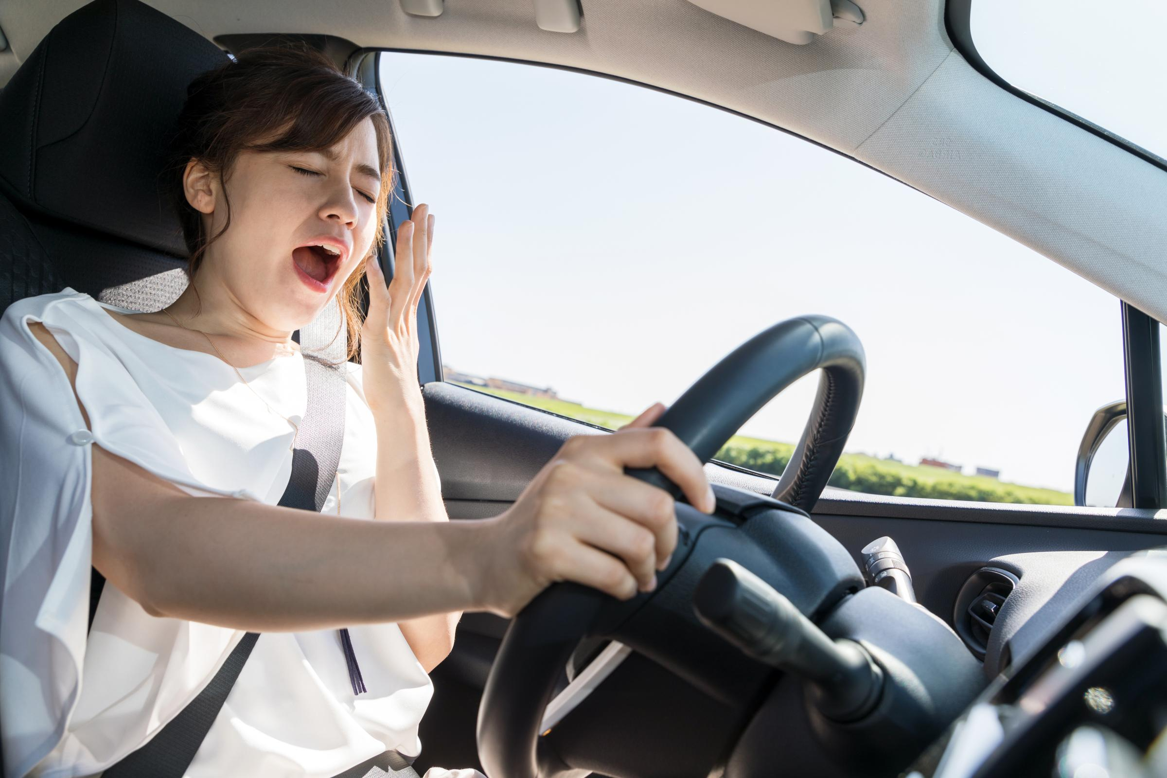 tired young woman yawning while driving her car - may cause car wreck