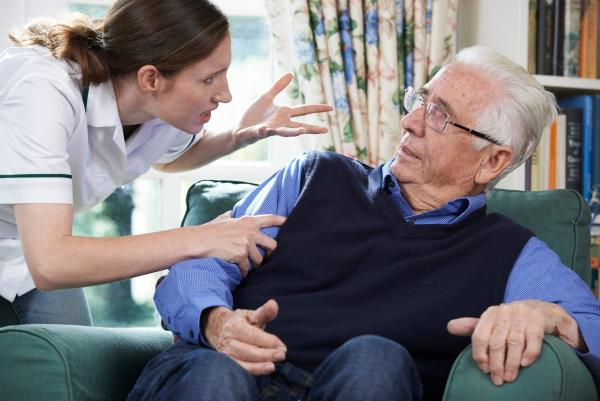 elderly man exeriencing emotional abuse from a nursing home worker