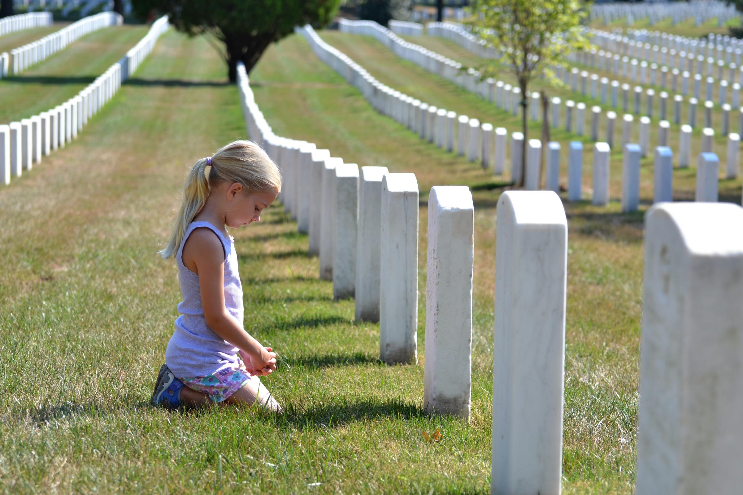 young girl in cemetery kneeling at grave of dead loved one