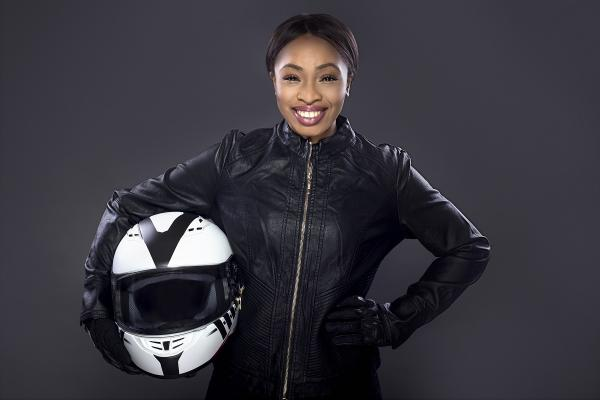 female motorcycle rider wearing protective gear - leather jacket and helmet