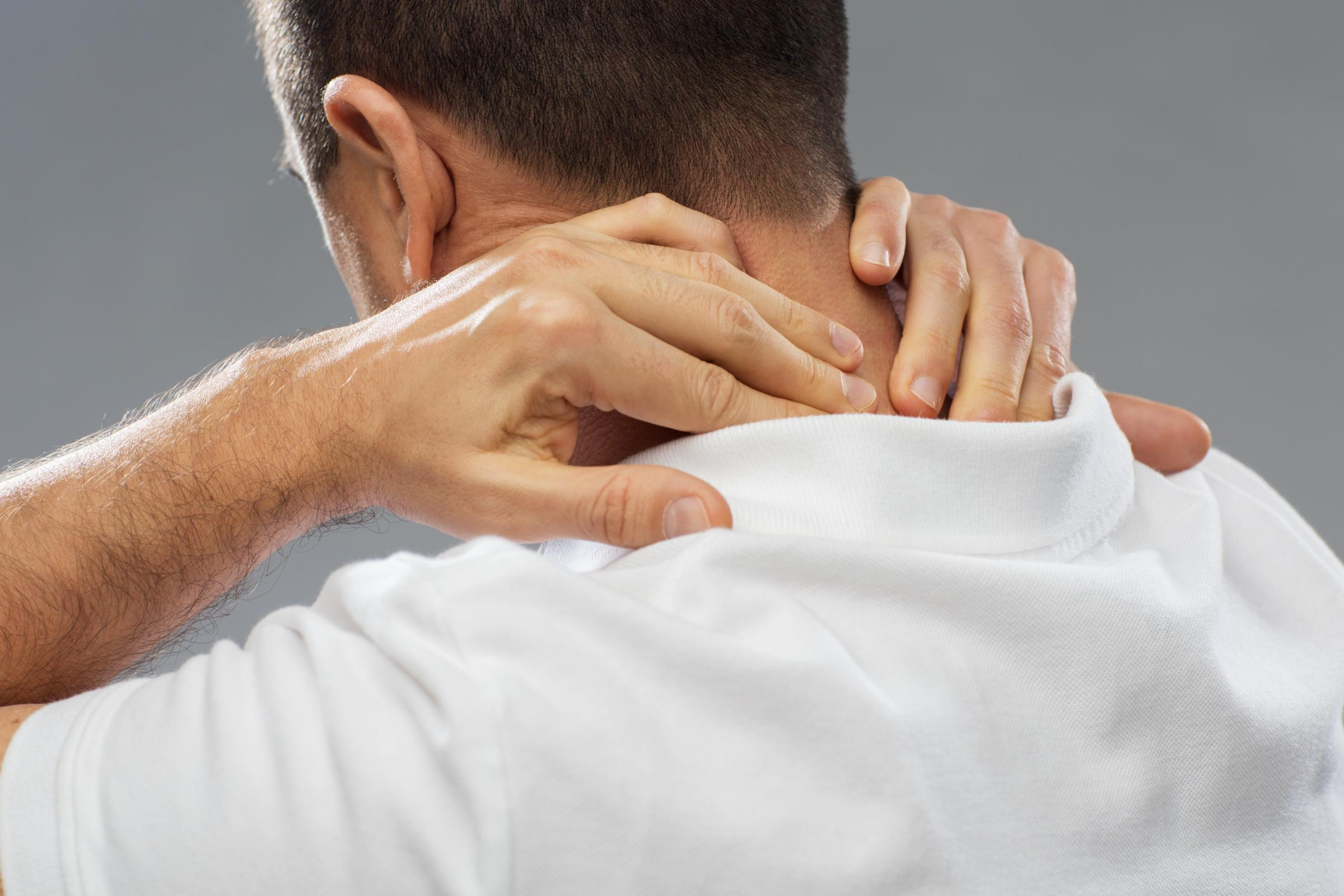 injured man touching the back of his neck