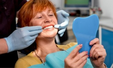 woman viewing her perfect smile at the dentist office