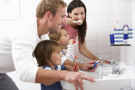 parents and kids brushing their teeth together