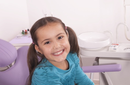 little girl in exam chair at the dentist office