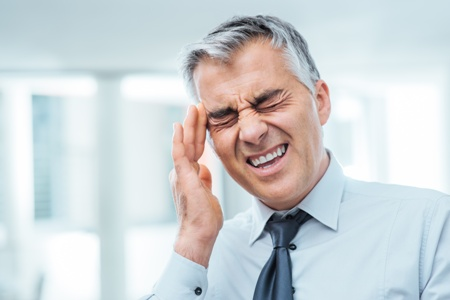 man with TMJ headache holding his temple