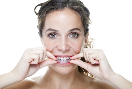 woman putting in her invisalign