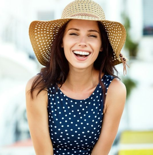 happy woman smiling in a sunhat