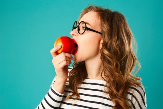 young woman with dental implants biting into an apple