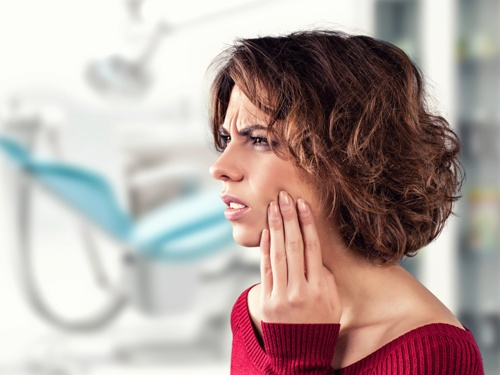 woman in dentist office with tooth pain