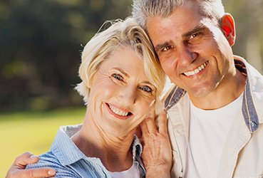 MIddle-Aged Couple Smiling in the Sun - Dental Implants by Dr. Clancy