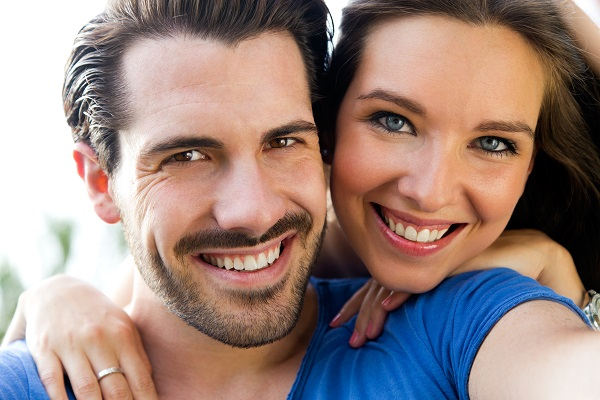 Close up of a couple smiling after full face orthodontic treatment
