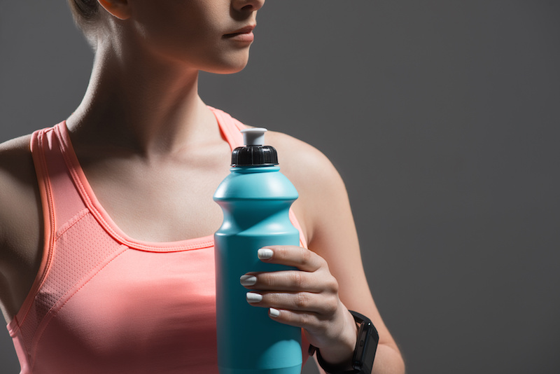 Woman holding a water bottle, in exercise clothes