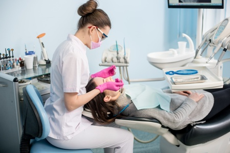hygienist cleaning woman's teeth