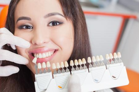 smiling female patient with teeth whitening shade guide