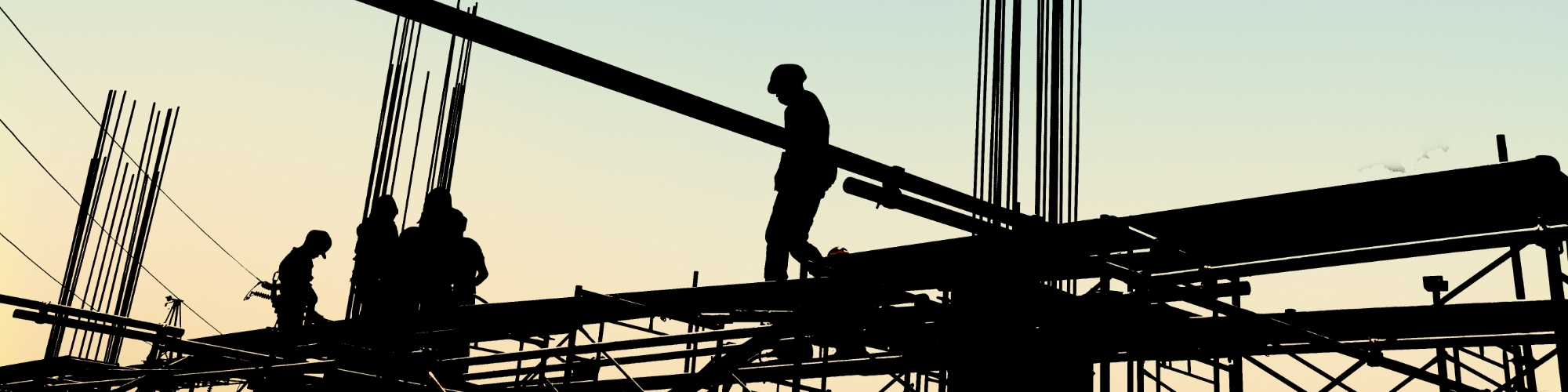 Silhouette of a man on steel beams working