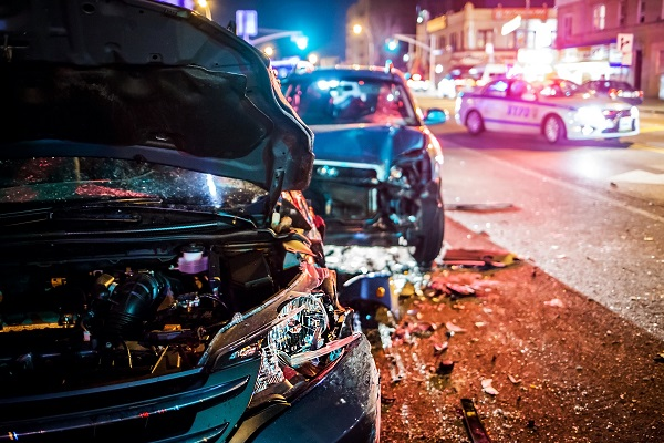 Image of a police vehicle at the scene of a car wreck at night