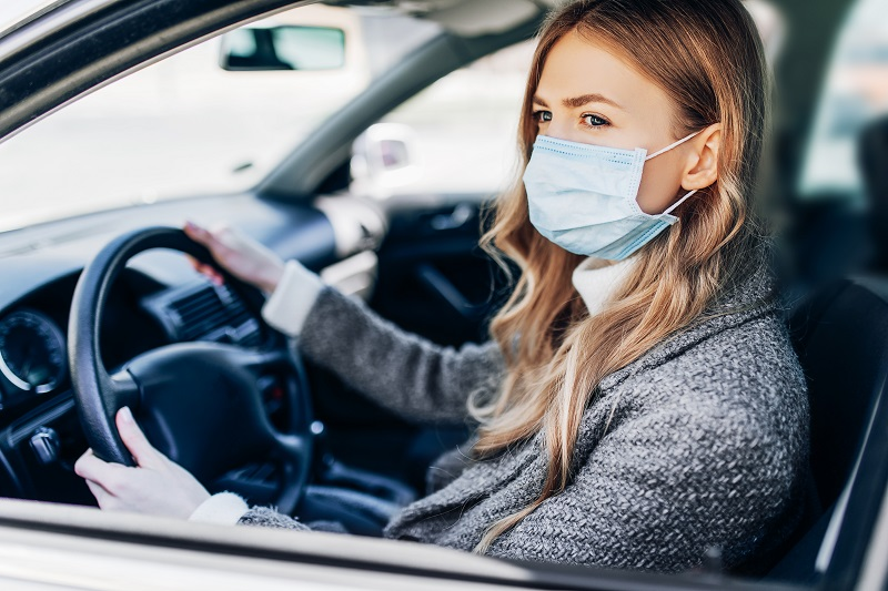 Woman driving while wearing face mask