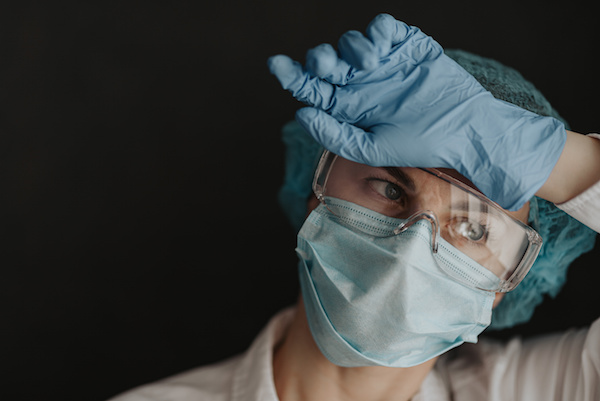image of an essential worker in protective mask and gloves resting her hand against her forehead.