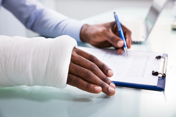 An injured person in an arm cast reviews a document