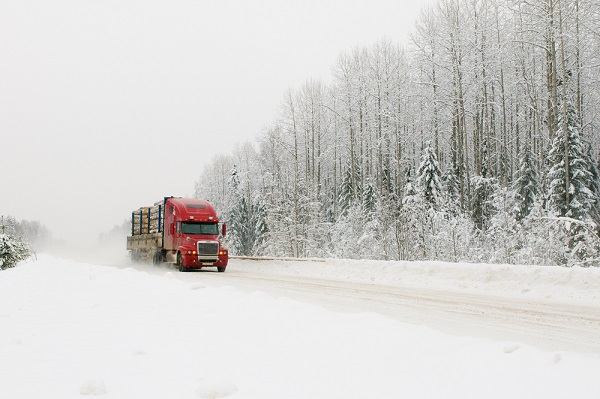 Semi truck driving across a snowy interstate and hauling logs