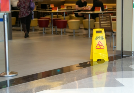 caution: wet floor sign at the entrance to a food court