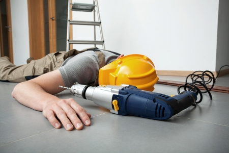 construction worker collapsed on floor next to power drill