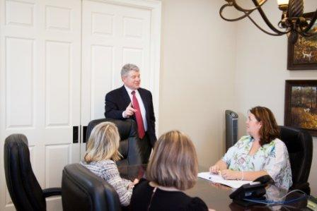 Gary Bruce standing in law office conference room speaking to staff