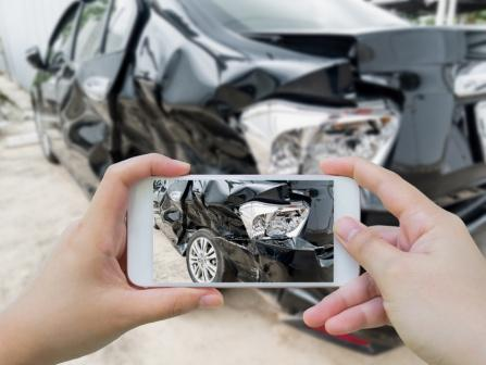 hands holding a smartphone taking a picture of a car damaged in an auto accident