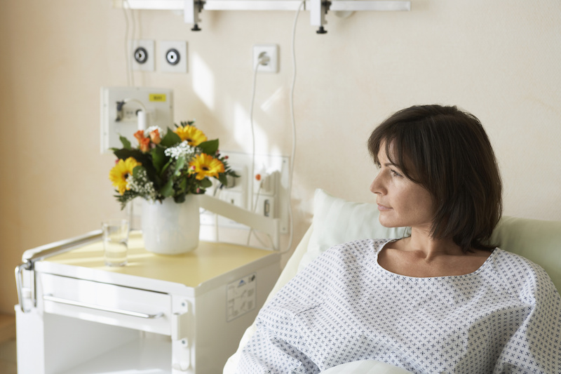 Sick woman in hospital bed with flowers on bedside table