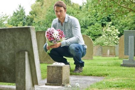 young man bringing flower bouquet to the grave of a deceased loved one