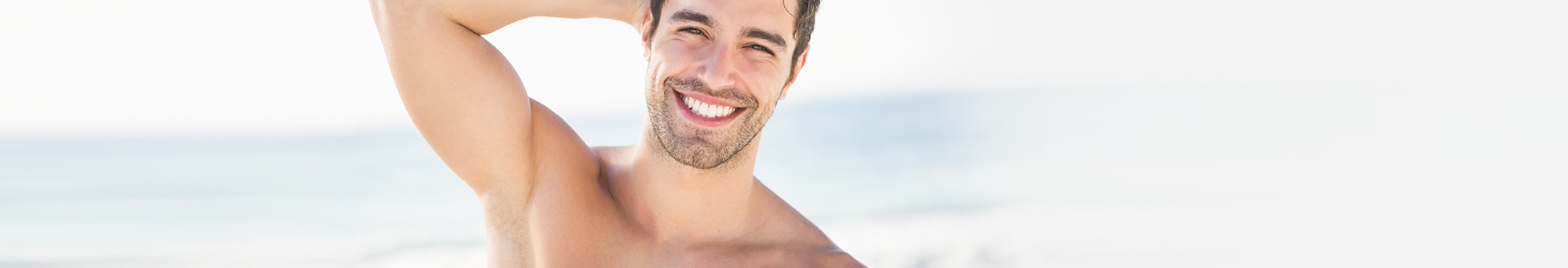 Dark haired man smiling and little facial hair