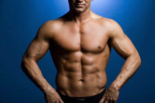 shirtless man with hands on hips showing pecs, abs